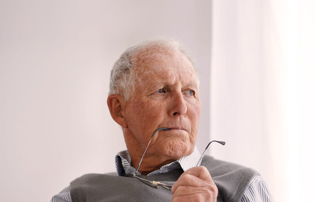 Older gentleman thinking with his glasses arm in his mouth