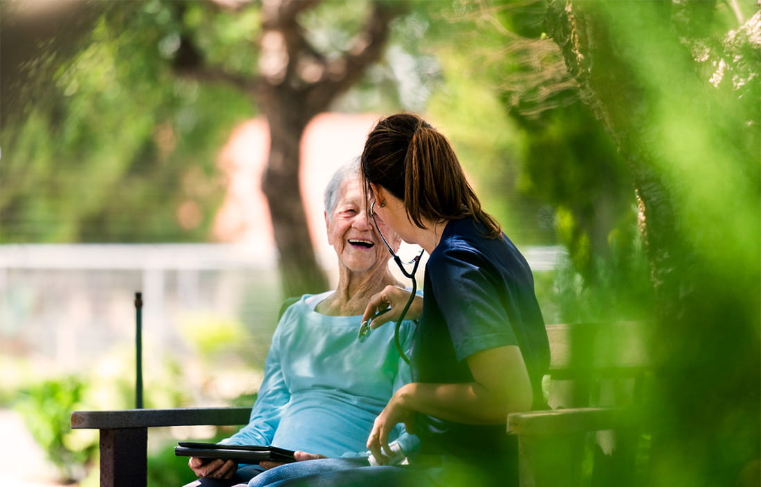 Senior mother and female care taker cheerfully talking on a park bench