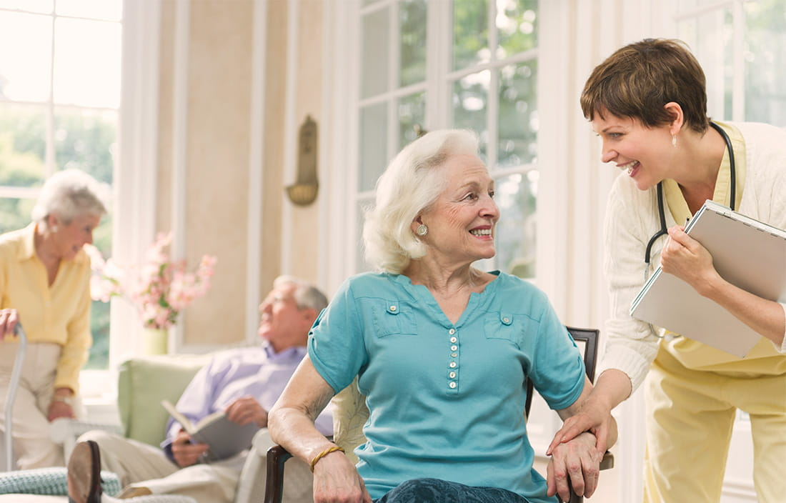 Senior woman cheerfully speaking with her female caretaker in a senior living facility