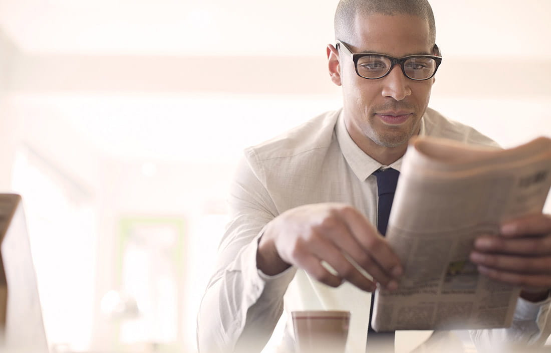 Business man sitting at a counter with a cup of coffee reading a newspaper