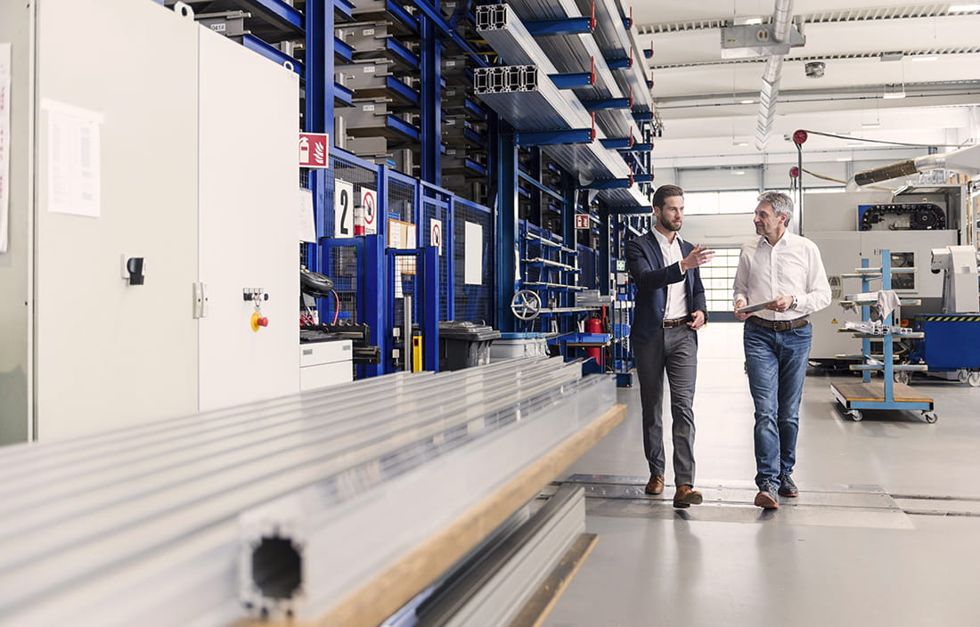 Two professionals walking on a manufacturing plant floor