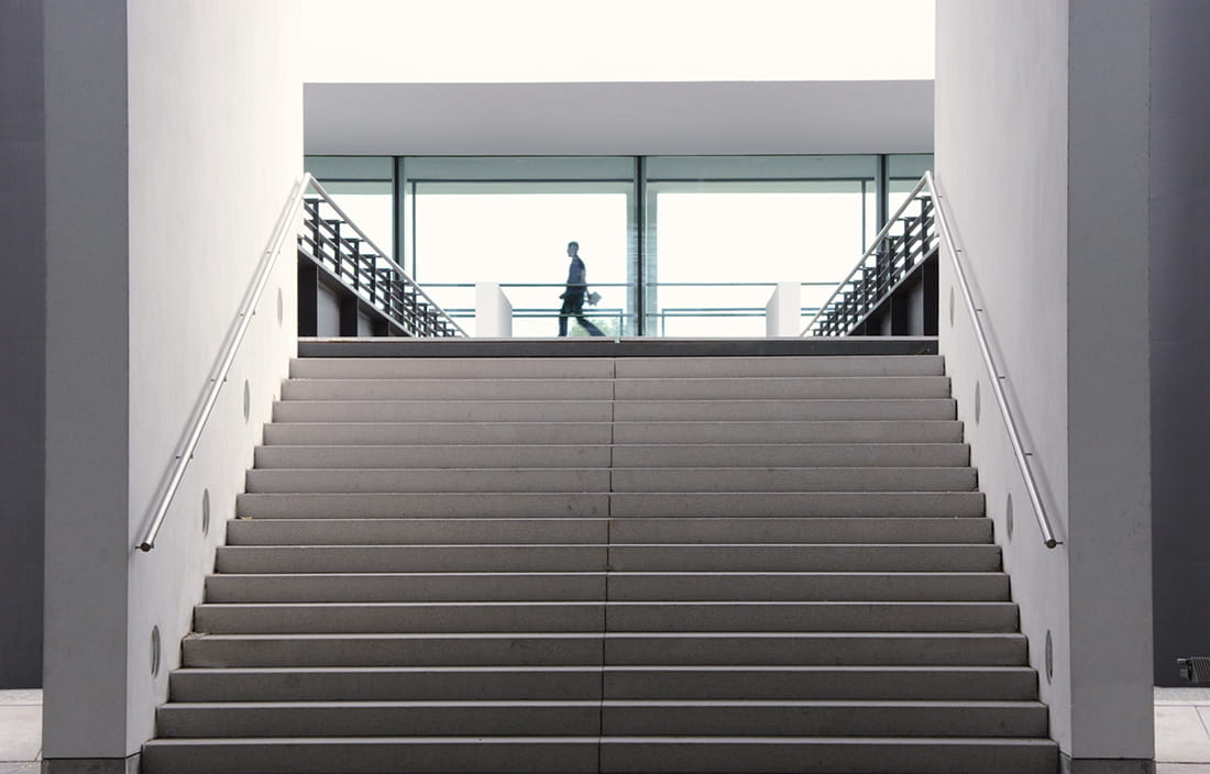 One person walking by a large staircase