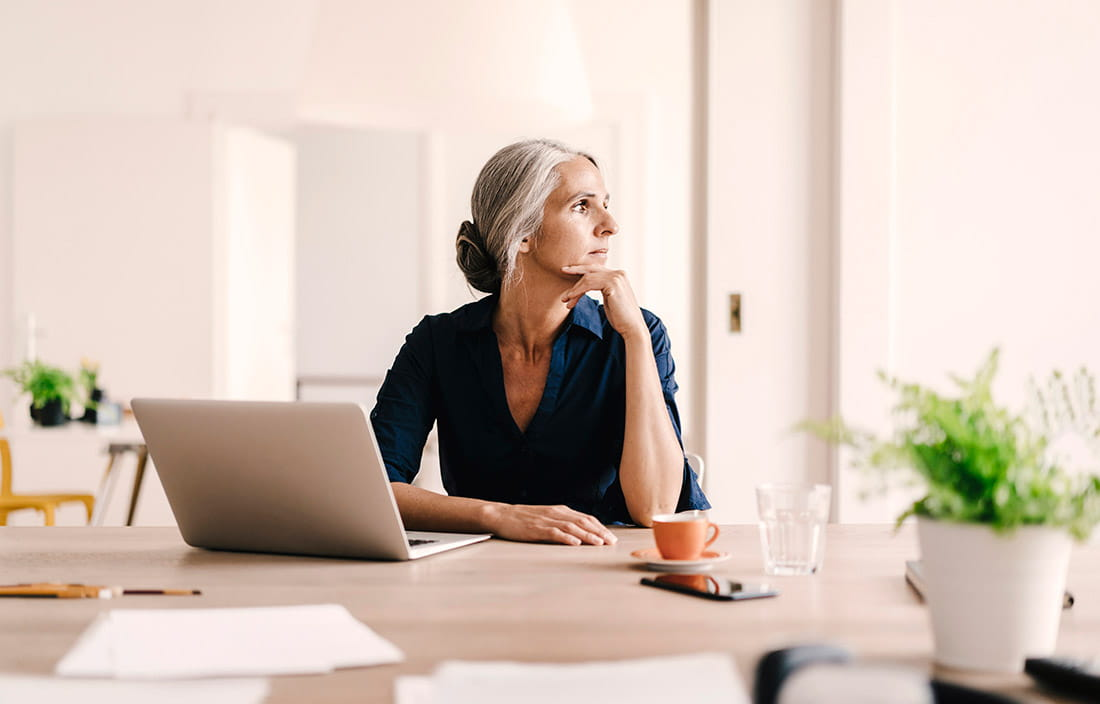 Woman sitting at her desk looking out the window