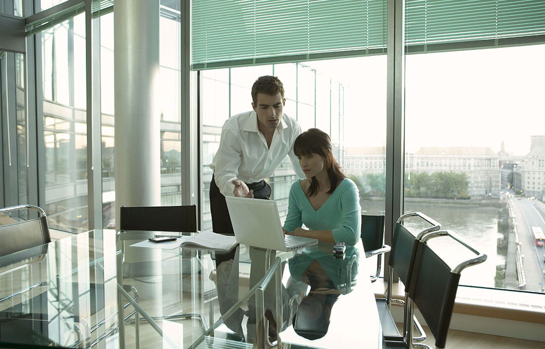 Man and woman looking at a laptop in a glass office