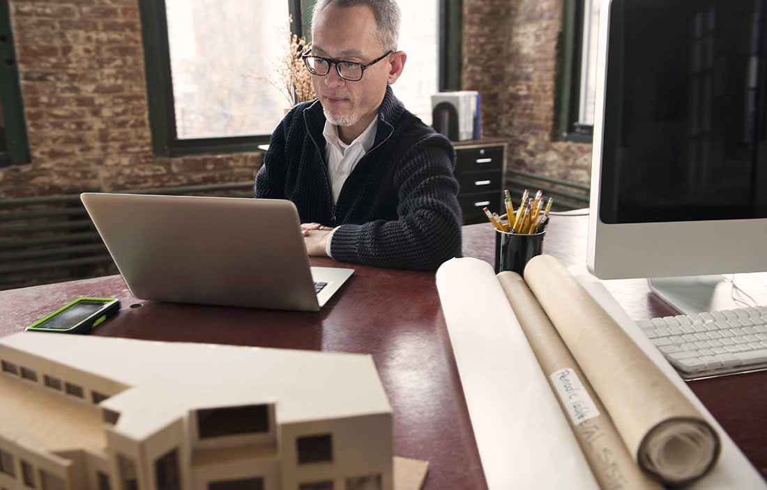 Man sitting at his real estate and construction desk typing on a laptop
