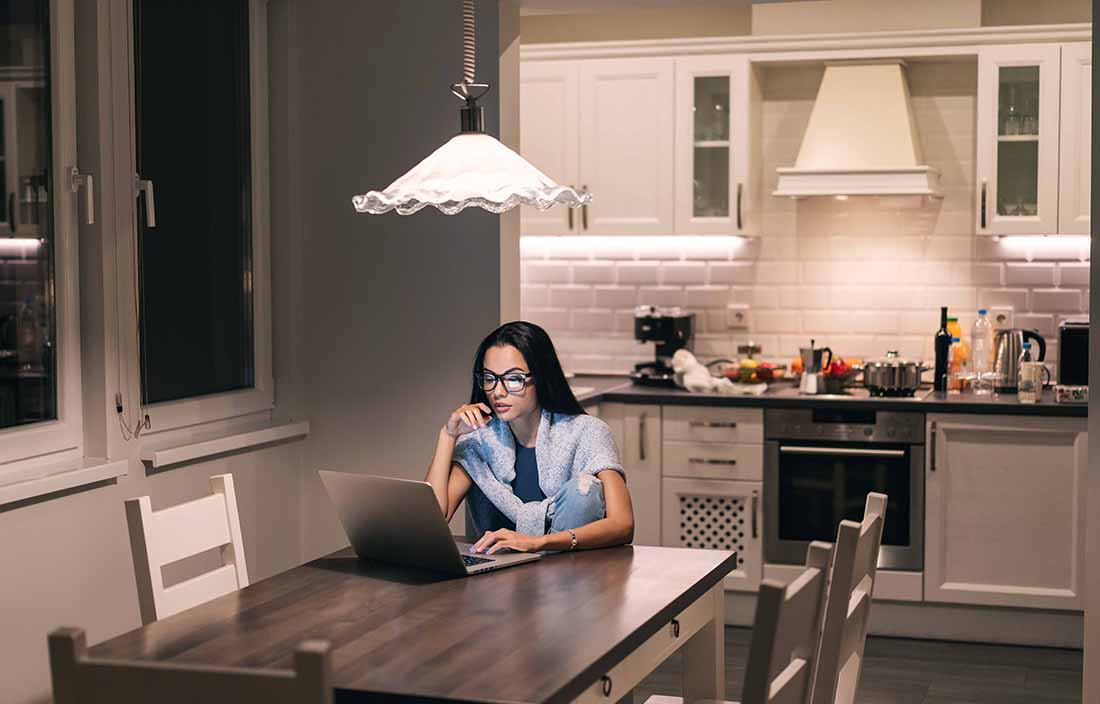 Woman sitting at the kitchen table on her laptop