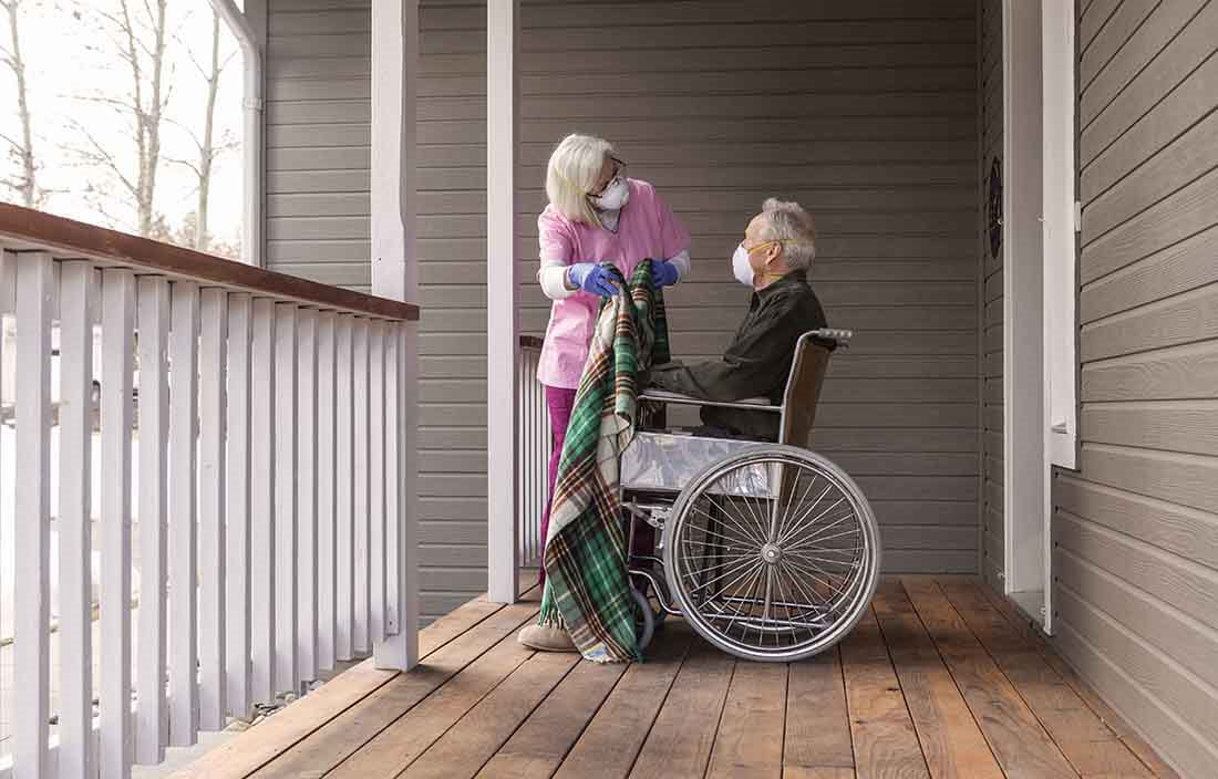Elderly man in wheelchair sitting on his front porch at home.