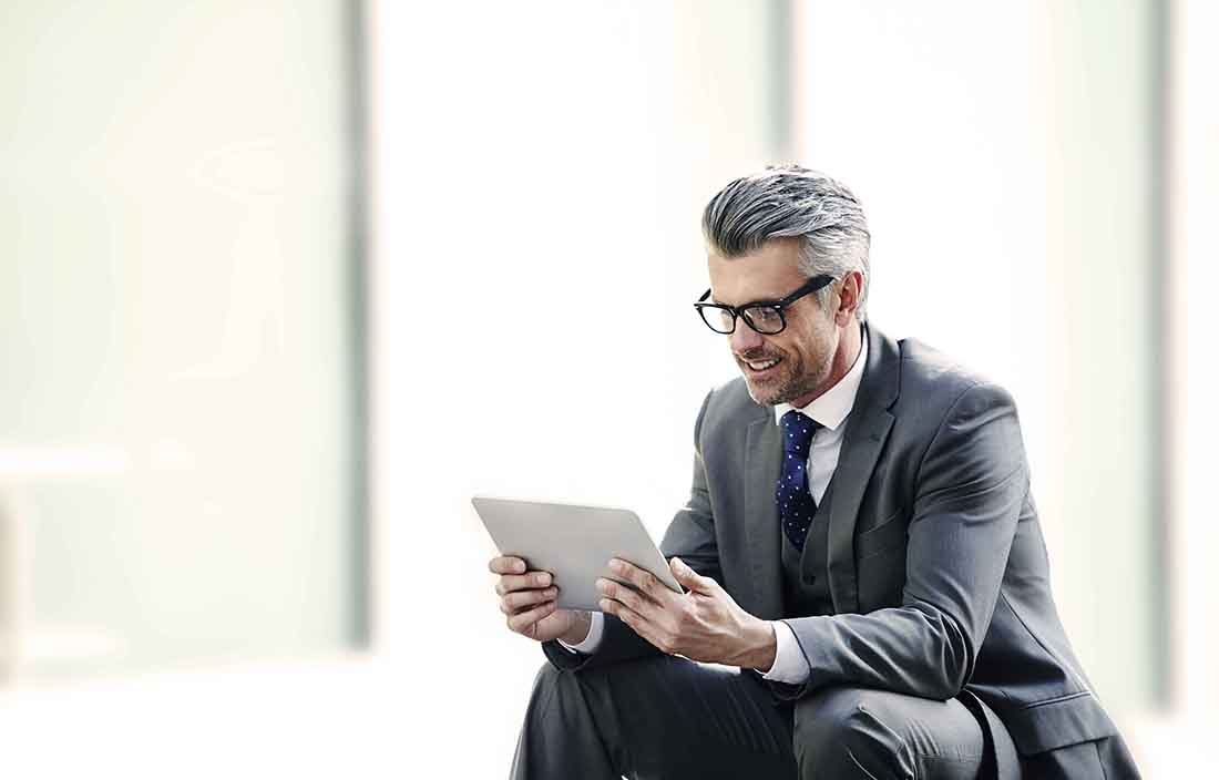 Man in suit reading on a tablet