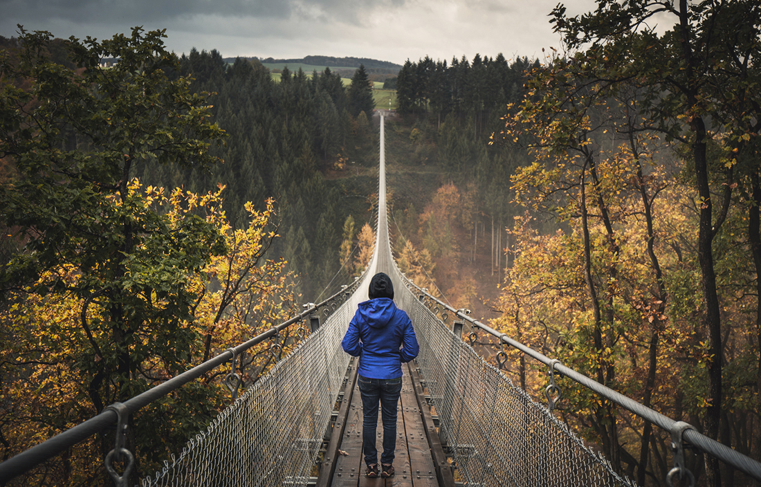 Person walking across a suspension bridge