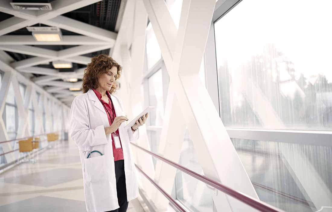 Doctor standing on a walkway using a handheld tablet device.