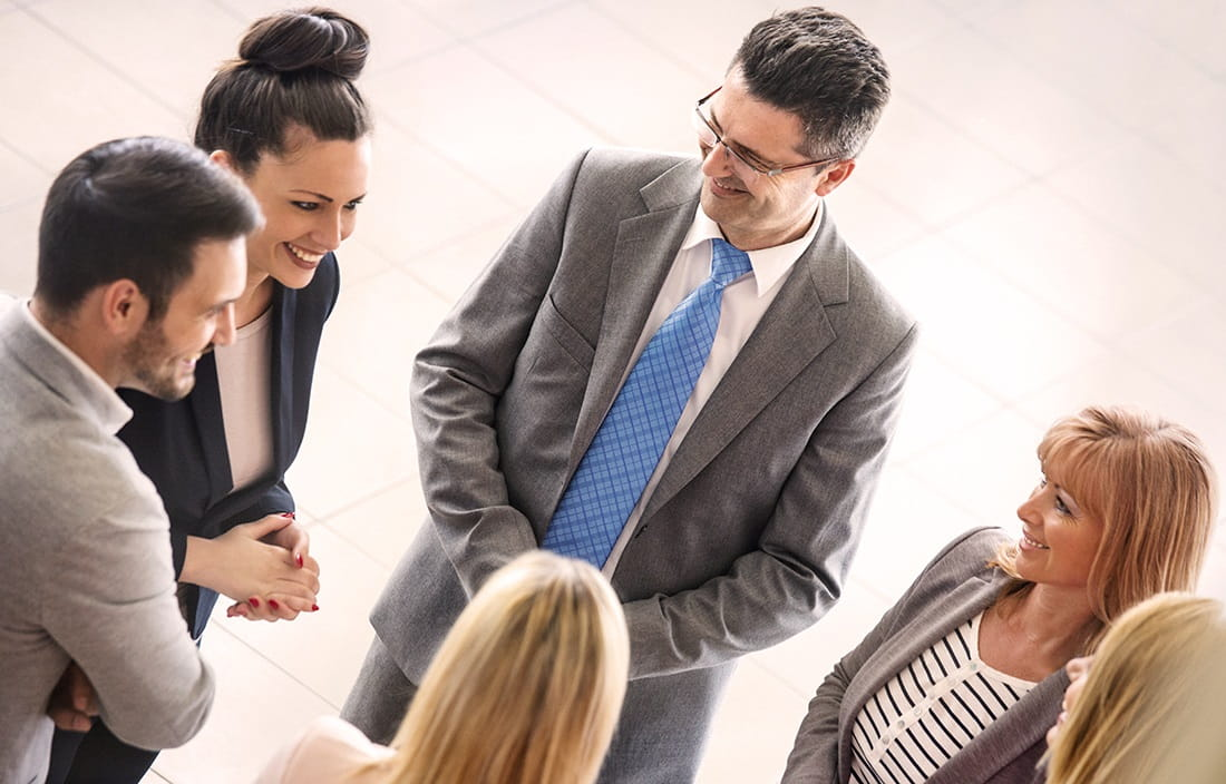 Image of business people standing in a circle talking.