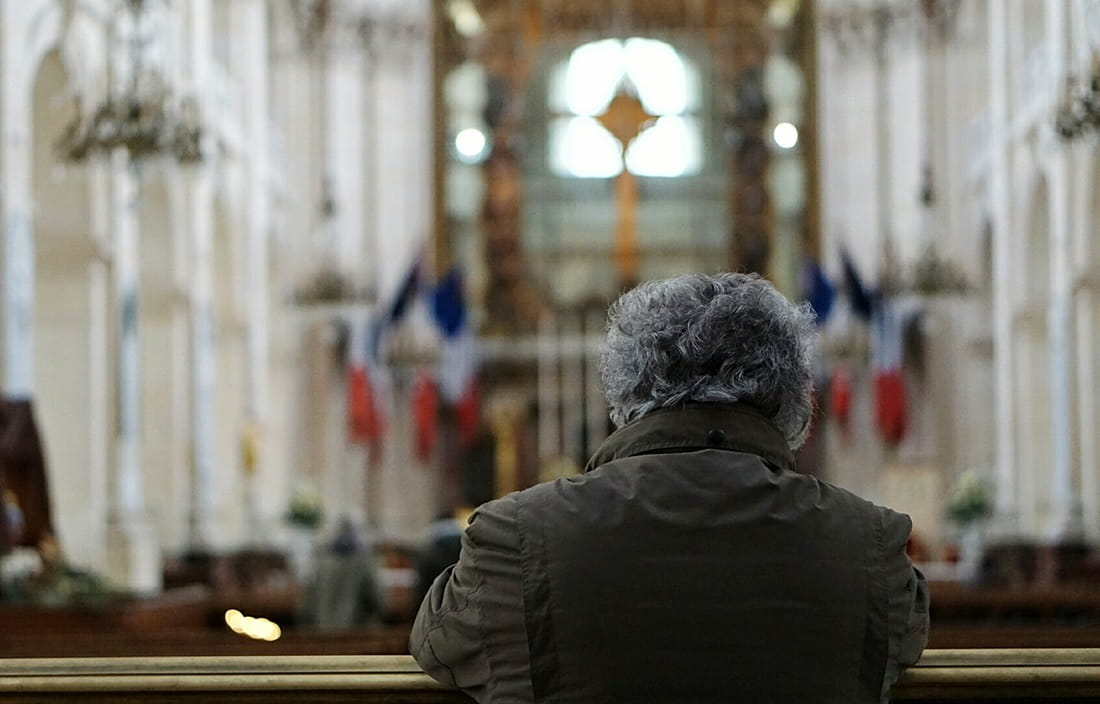 Image of man kneeling in church pew.