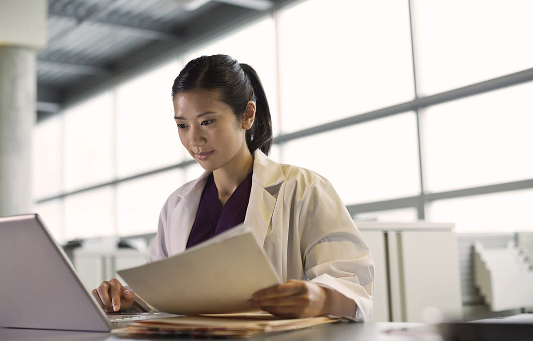 Image of female doctor sitting at a computer and holding paperwork.