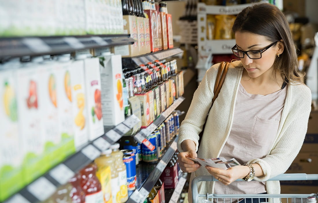 Image of woman in grocery store aisle looking at coupons.