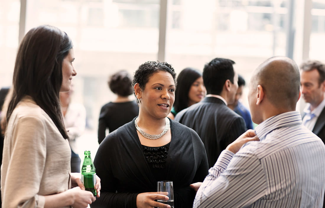 Image of three people talking during business networking event.