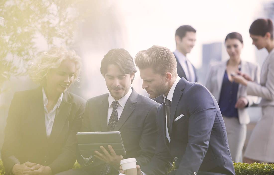 Image of three business people sitting outside looking at tablet computer together.