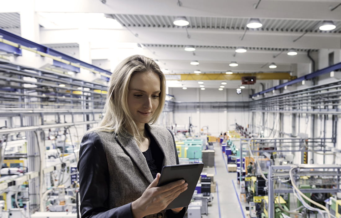 Woman on factory floor with tablet