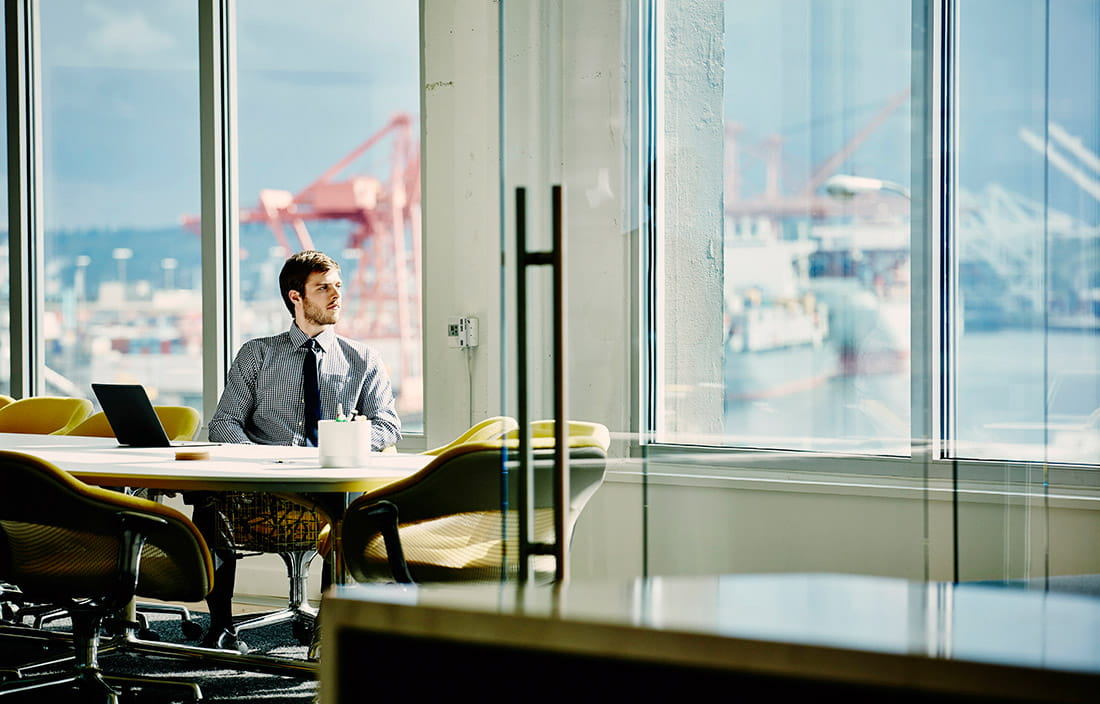 Business person sitting at his desk looking out the window.