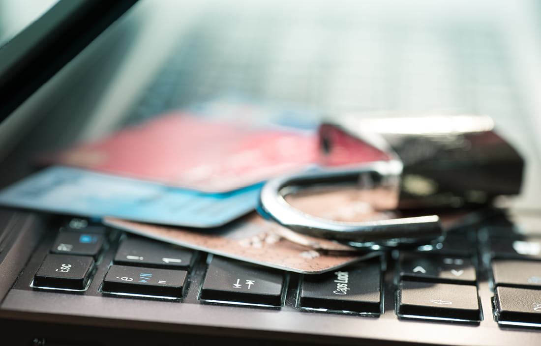 Padlock and credit cards on top of laptop keyboard.