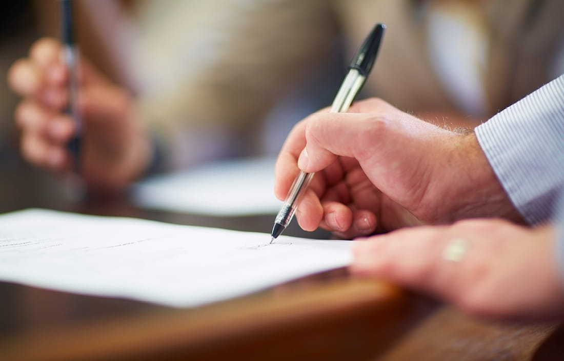 Man signing document with pen.