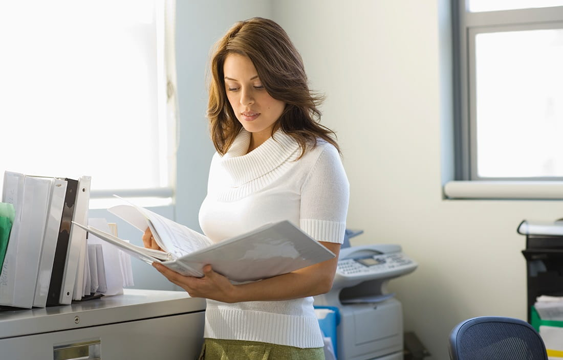 Image of woman in office reading papers in a three ring binder.
