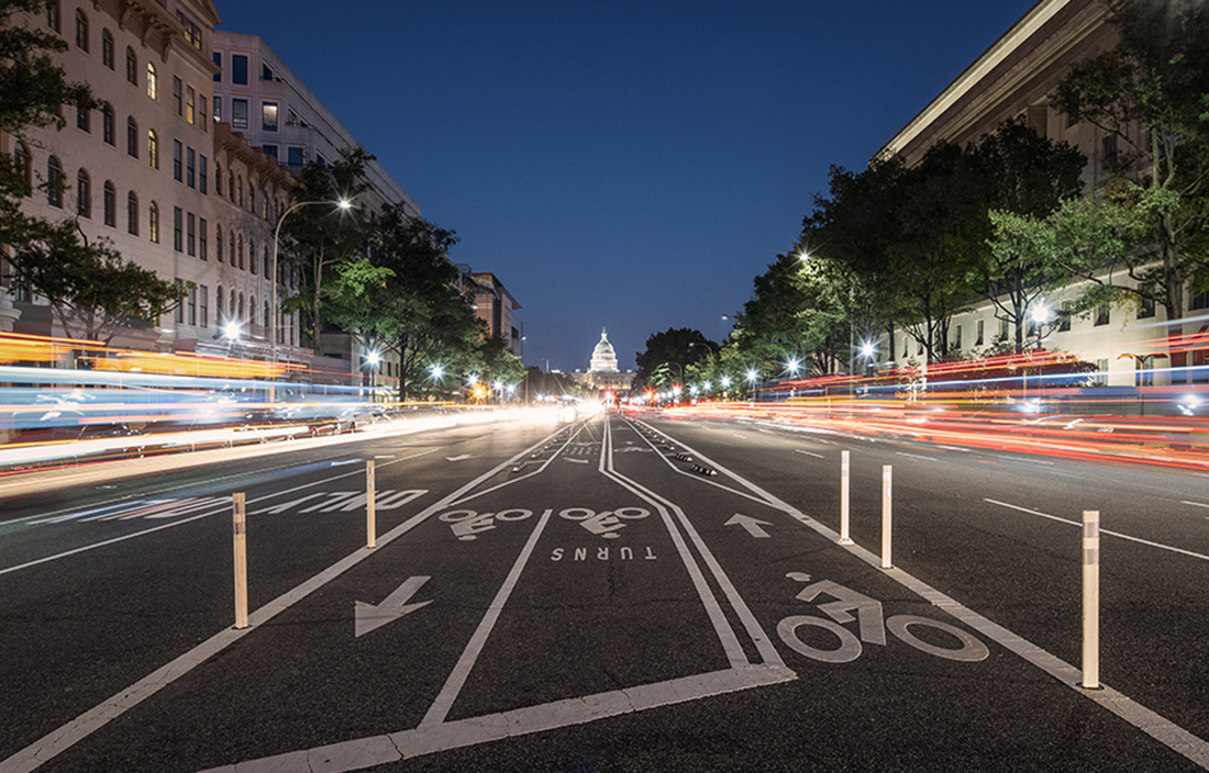 Picture of a busy street with the US capitol in the distance