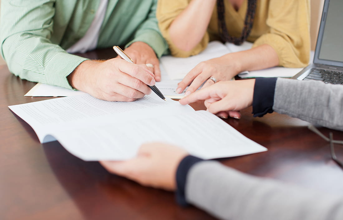 Close-up image of three people's hand, reviewing documents.