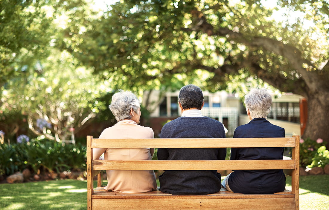 Three elderly senior citizens sitting on a park bench.