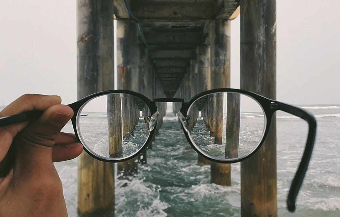 A photo of eye glasses bringing something into view/clarity