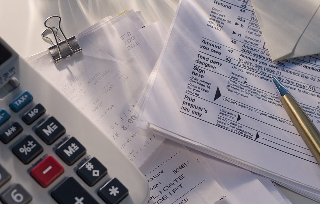 Close up image of calculator and tax paperwork on a desk.