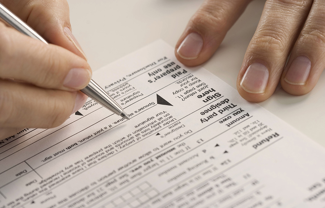 Close up of a tax document being filled out by a person.