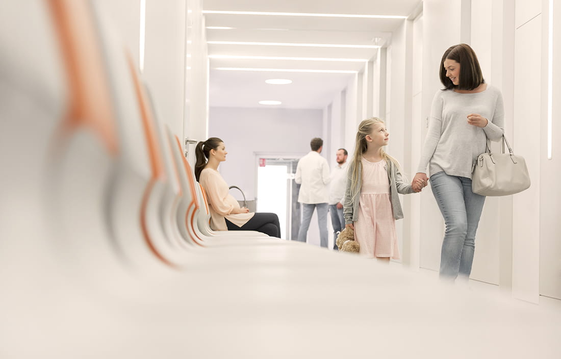 Mother and daughter walking in a hospital