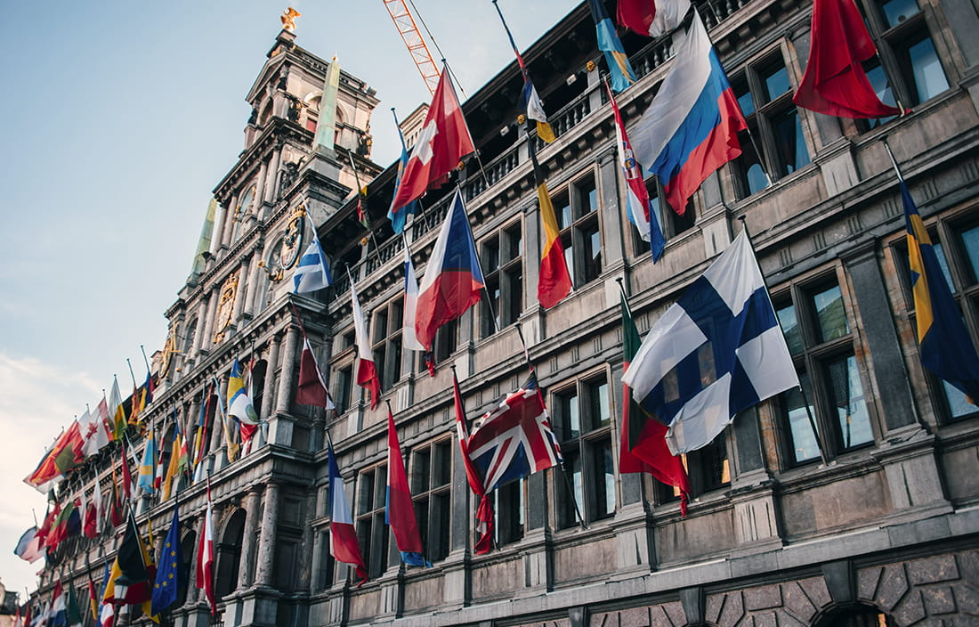 Image of city hall in Antwerp, with flags from many countries.