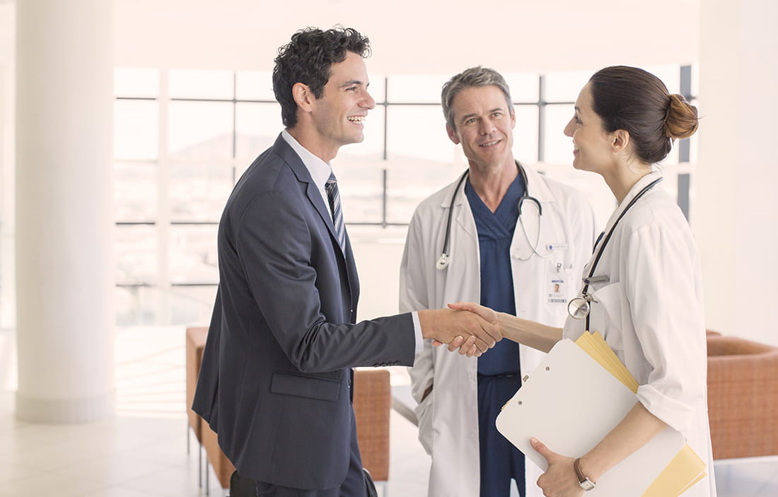 A man in a suit is shaking a female doctor's hand and a male doctor is standing next to them.