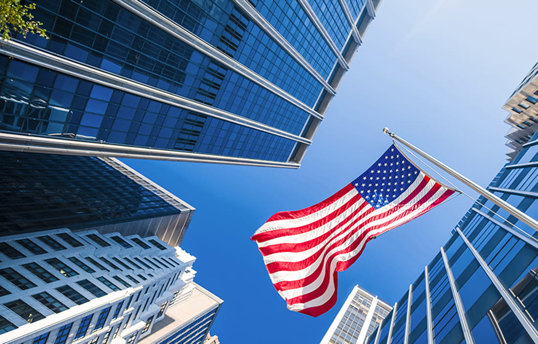 Image of American flag flying between buildings