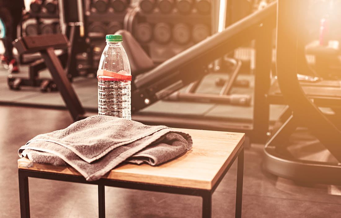 Picture of a water bottle on a bench next to gym equipment.