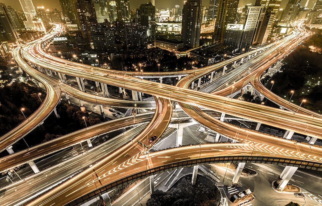 Picture of a busy highway intersection at night.