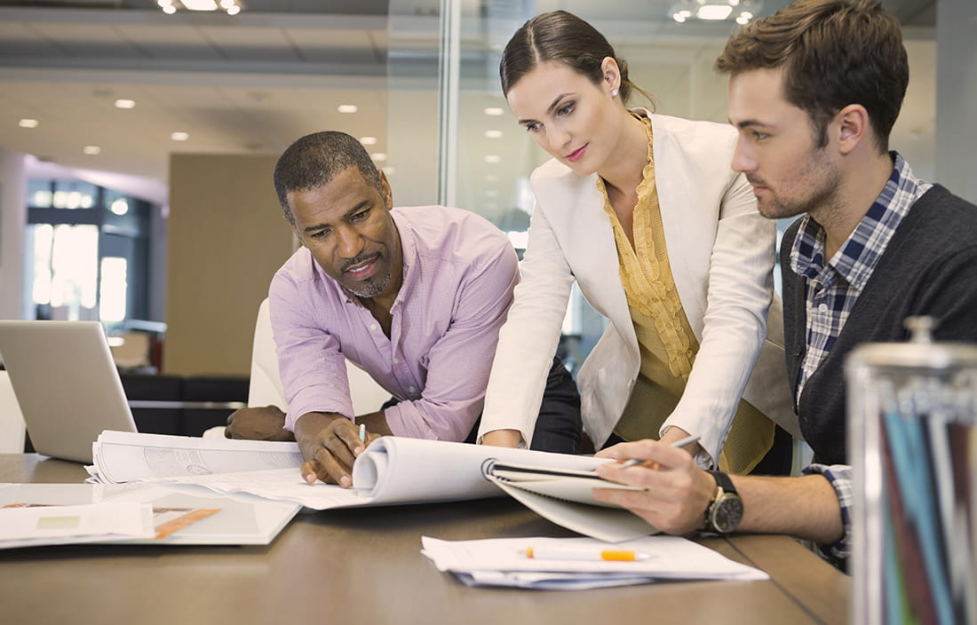 Image of three business people reviewing documents in an office.