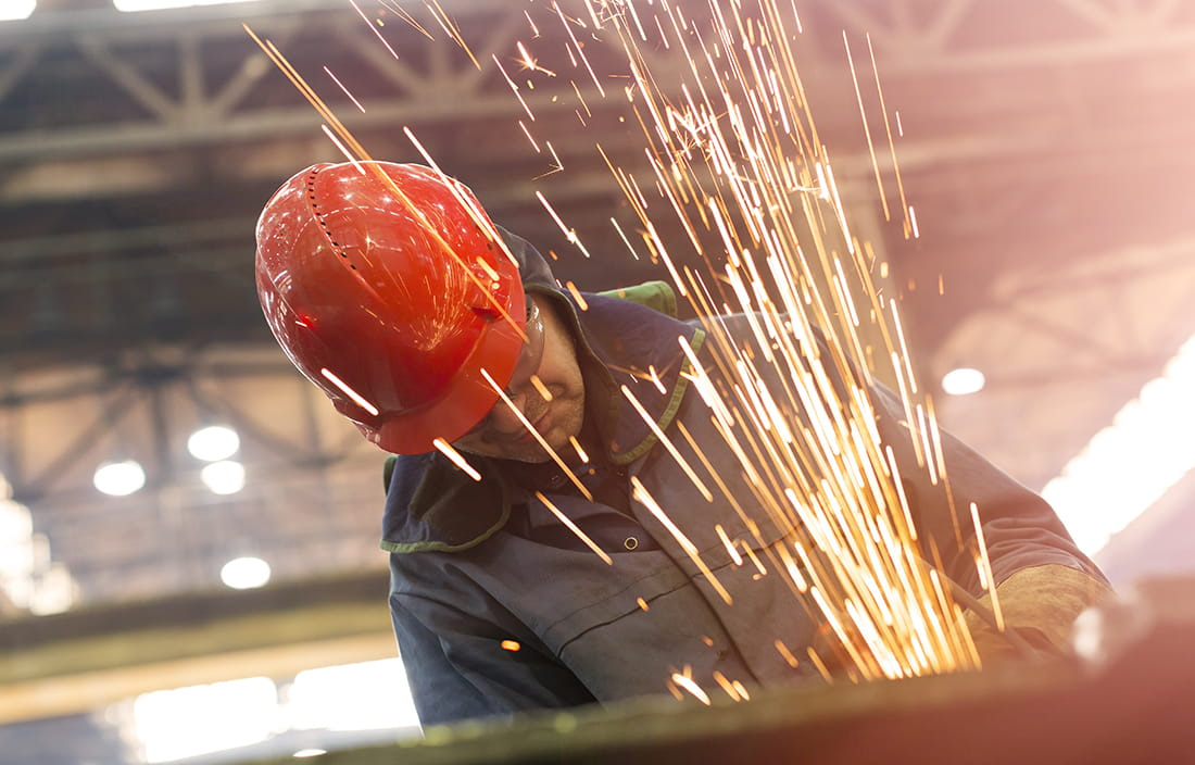 Image of a man at a construction site wearing a red hardhat and safety glasses with sparks flying in front of him.