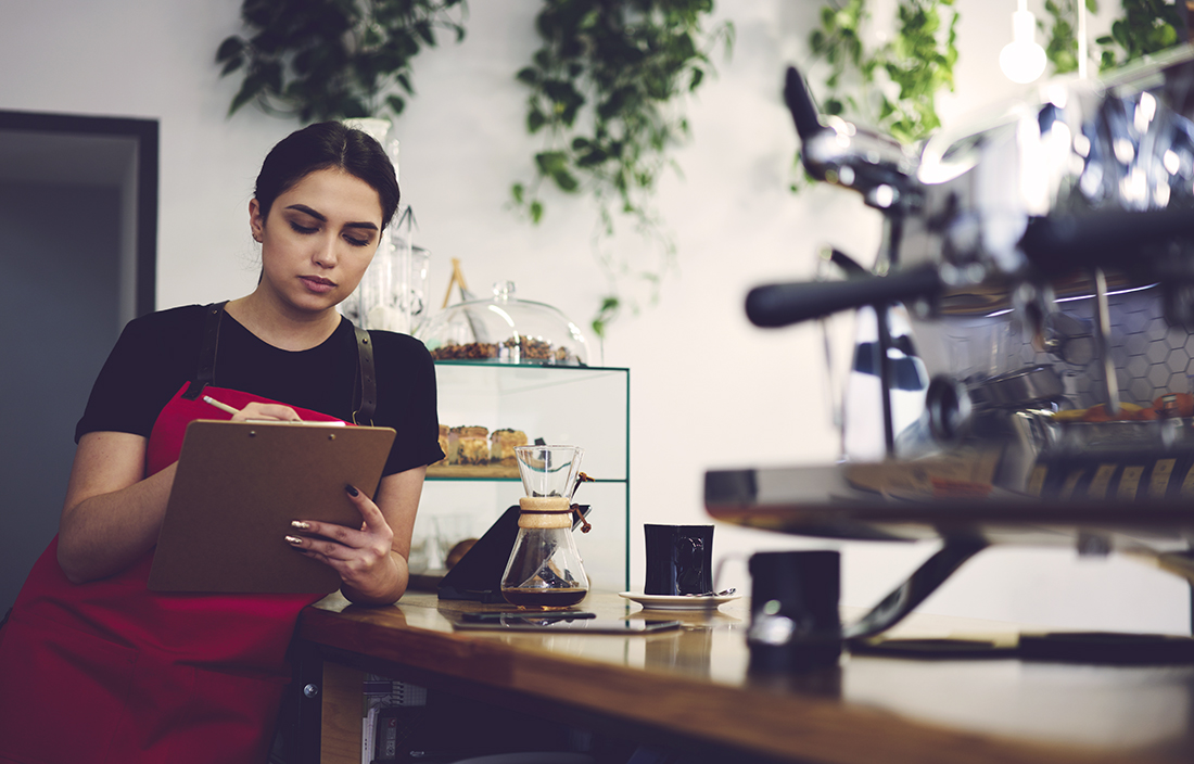 Image of a female barista holding a clipboard behind the coffee shop counter.