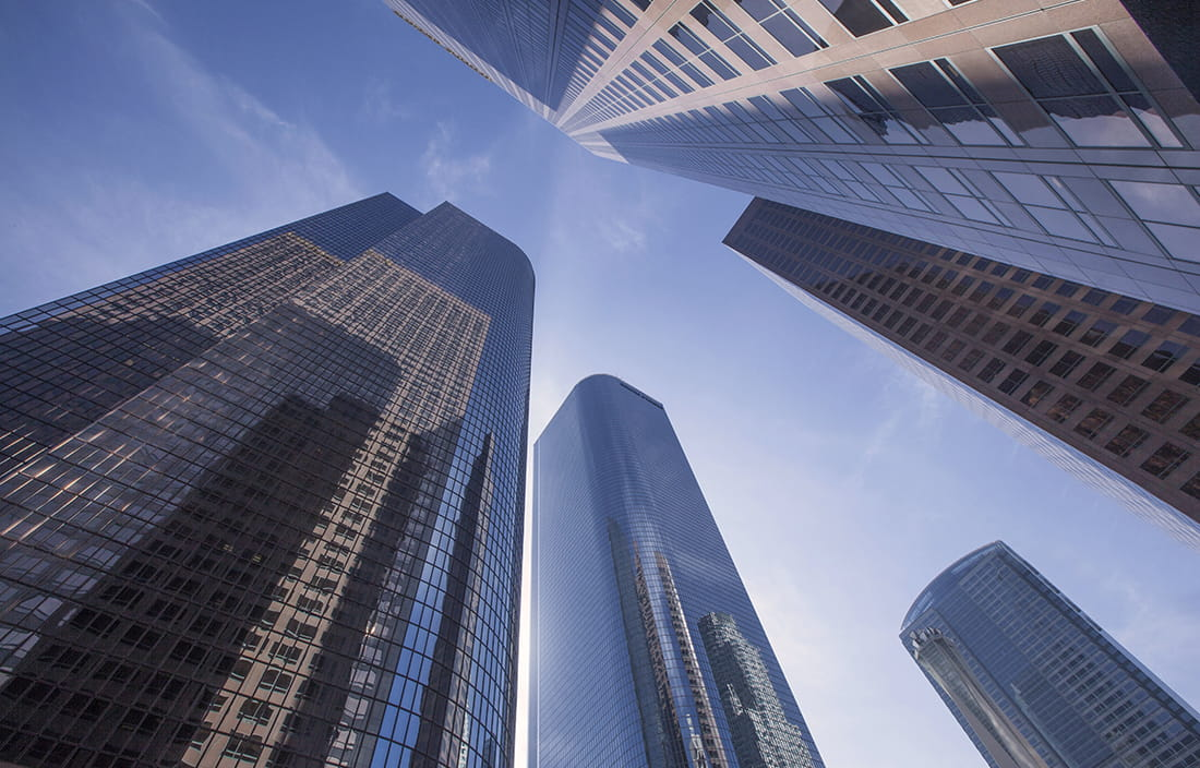 Image of skyscrapers from the ground perspective looking up.