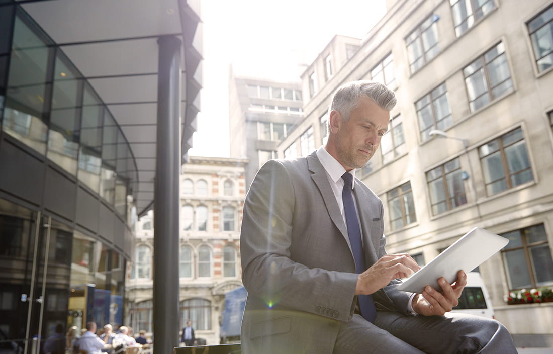 Business man using tablet device on a city street.
