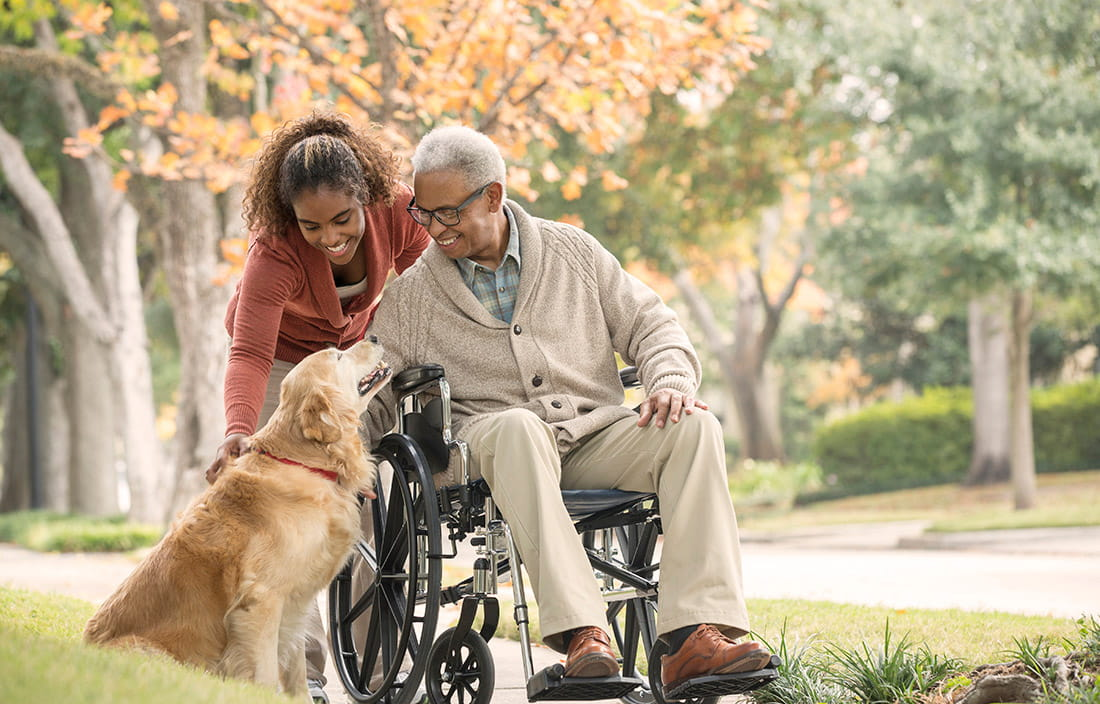 Image of a woman pushing an elderly man in a wheelchair outside and both petting a golden retriver dog.