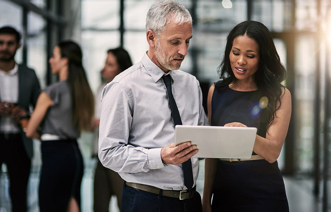 Image of business man and business woman looking at a document together.