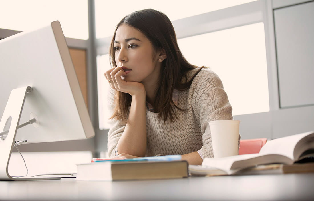Woman sitting at a computer desk researching retirement savings plans.