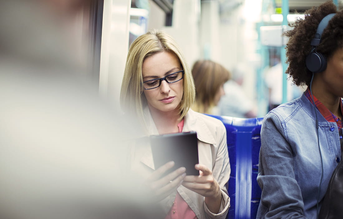 Woman sitting on subway train using her phone/tablet device.
