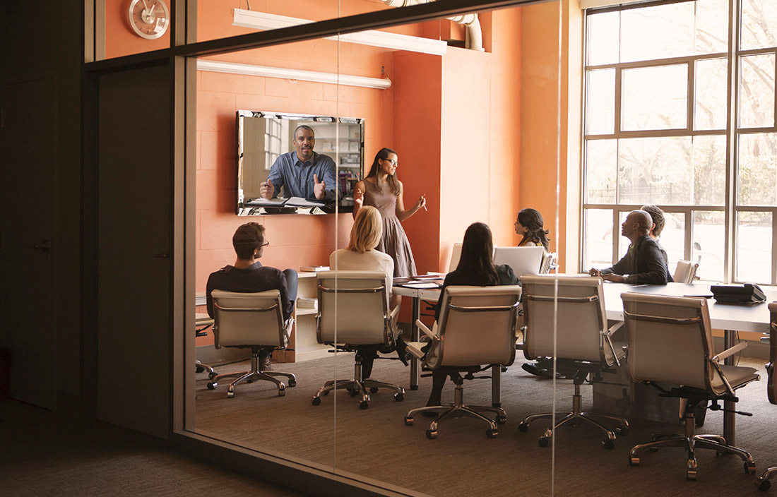 Image of people sitting in meeting room during video conference.