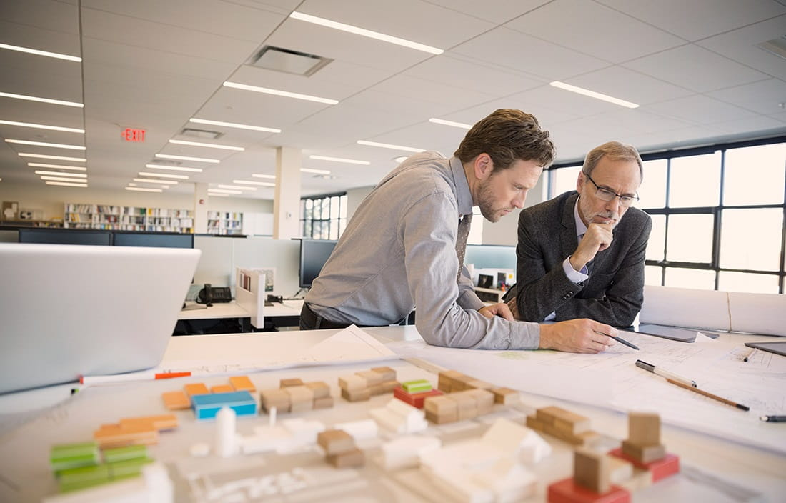 Image of two men in an office reviewing blueprints.
