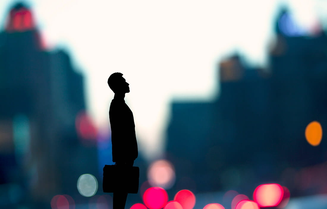 Photo of man with briefcase standing in front of blurred city scene.