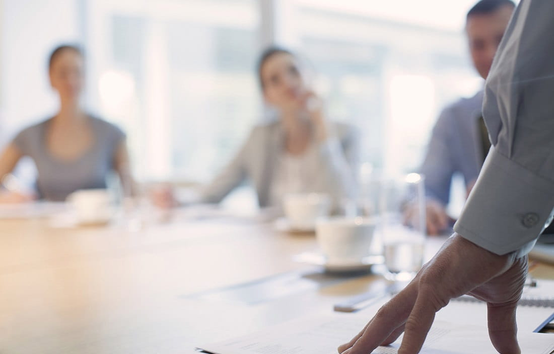 Image of businessman's hand on conference room table with other business people out of focus in the background.